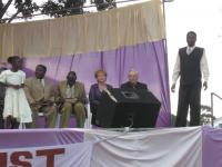 Amos Ouma Juma looking down at the Bible. Pastor Leo Strathman and Donna ready to preach at the Healing Crusade with the translator, Barak standing.